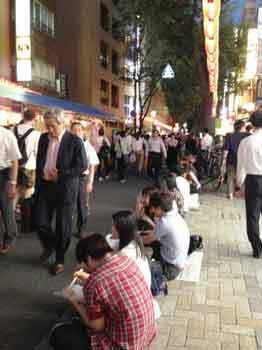 350ほおずき市06歩道に座って食べる人々.jpg